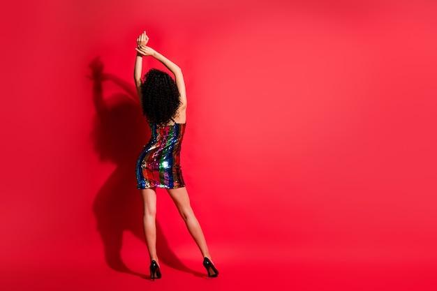Arrière arrière derrière vue sur toute la longueur du corps d'une jolie fille mince aux cheveux ondulés dansant profiter isolé sur fond de couleur rouge vif