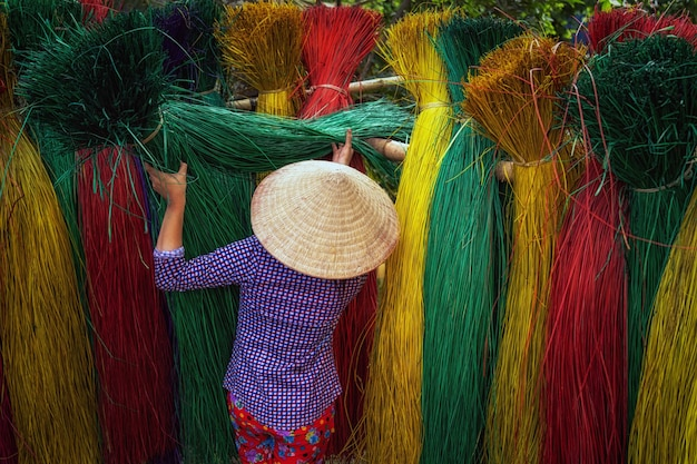 L'arrière d'une artisan vietnamienne séchant des tapis vietnamiens traditionnels dans l'ancien traditionnel