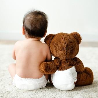 L'arrière d'un bébé avec un ours en peluche