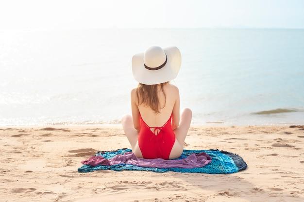 L'arrière de la belle femme en maillot de bain rouge est assis sur la plage