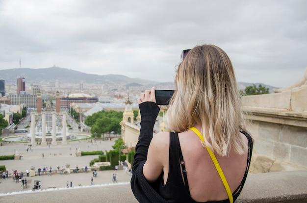 L'arrière de la belle jeune fille en chemise noire faisant une photo sur un téléphone du panorama de la ville de barcelone depuis le musée national de la catalogne et la cascade de fontaines à barcelone. catalogne, espagne.