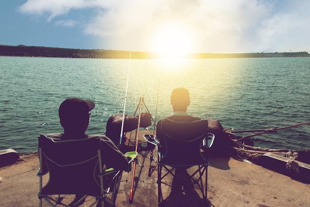 L'arrière de deux hommes sur le siège se détend du travail avec la pêche sur la jetée en mer au lever du soleil