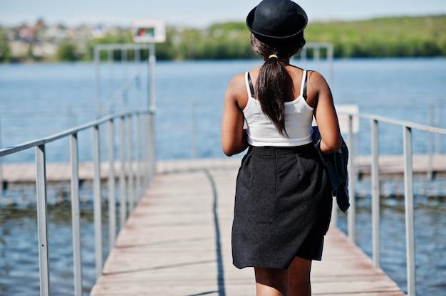 L'arrière du modèle afro-américain élégant en chapeau de lunettes, veste en jean et jupe noire posé en plein air sur la jetée contre le lac.