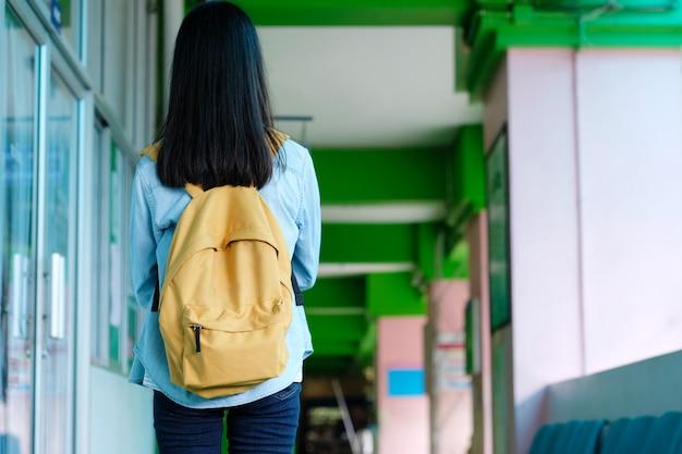 L'arrière d'une étudiante tenant des livres et un sac d'école pendant qu'il se promenait sur le campus