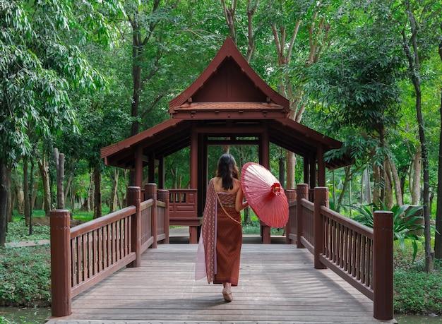 L'arrière d'une femme asiatique en costume traditionnel thaïlandais tenant un parapluie rouge marchant sur un pont dans un ancien pavillon en bois dans un parc d'arbres verts