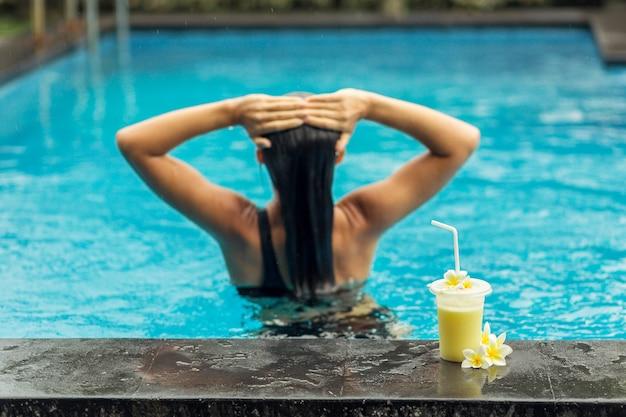 L'arrière de la femme dans la piscine avec des fruits secoués.