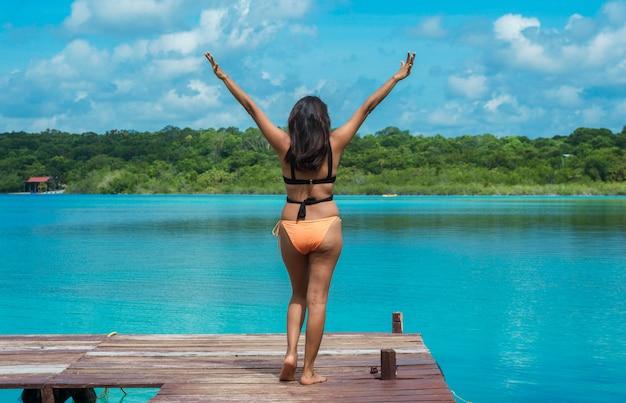 L'arrière de la femme heureuse avec les bras tendus au-dessus du quai. bacalar, quintana roo, mexique