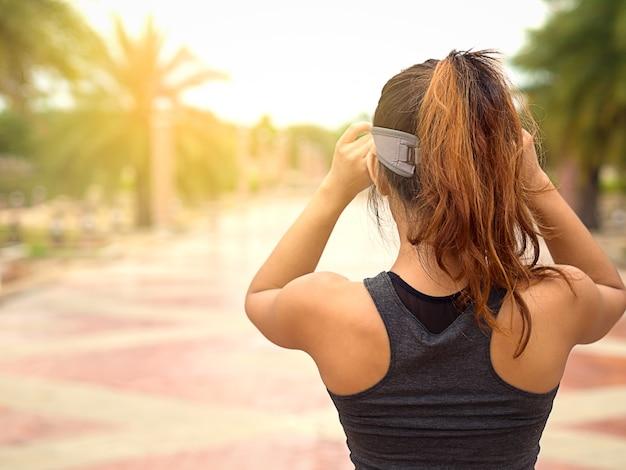Arrière de la femme de sport touchant sa casquette de sport sur la route, prêt à commencer à courir