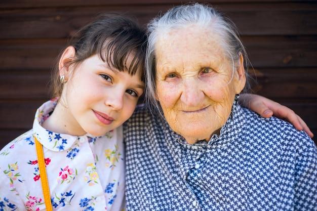 Arrière-grand-mère et arrière-petite-fille assises bras dessus bras dessous.