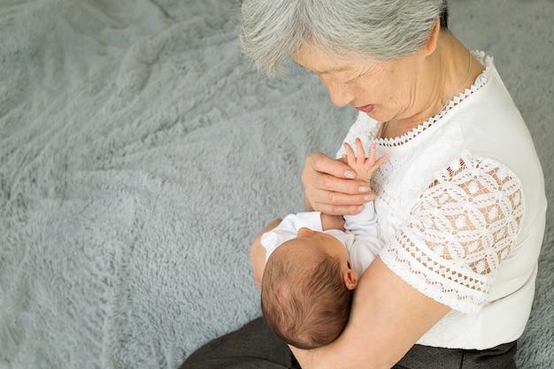 L'arrière-grand-mère joue avec une arrière-petite-fille nouveau-née.