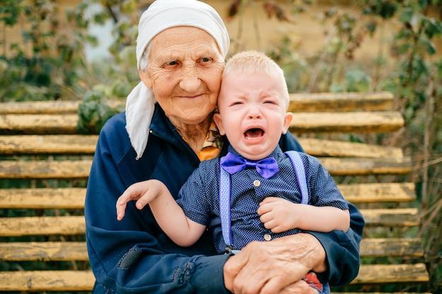 Arrière grand-mère tenant pleurer arrière petit-fils sur ses genoux en plein air.