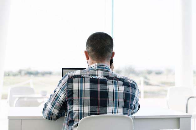 L'arrière d'un homme travaillant devant l'ordinateur portable et parlant au mobile