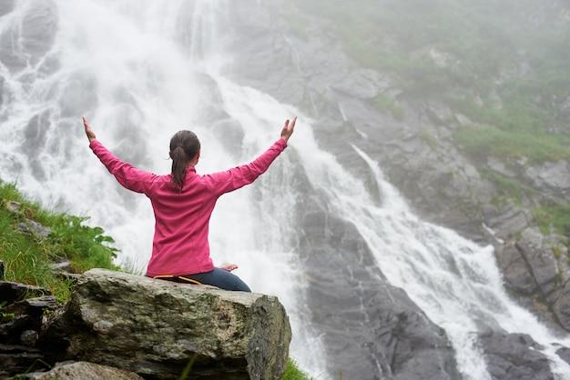 L'arrière de la jolie jeune femme assise sur un gros rocher à la grande cascade puissante. belle fille, apprécier, les, nature, brumeux, temps