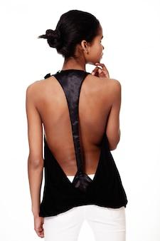 L'arrière de la mode élégant souriant décontracté jeune femme belle fille noire américaine en vêtements noir et blanc sur fond blanc