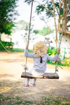 L'arrière de la petite fille asiatique portant un chapeau assis sur une balançoire dans le parc