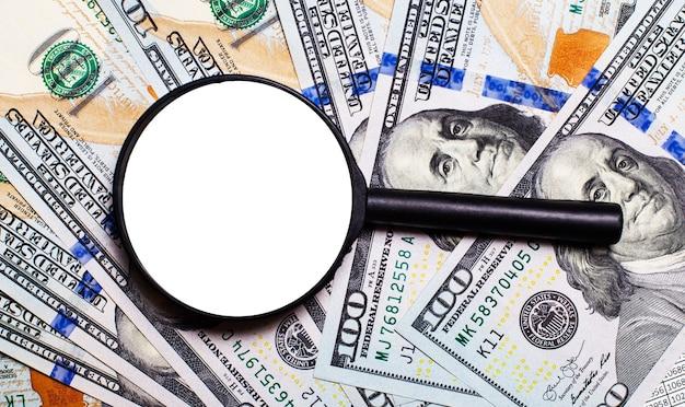 Arrière-plan avec des billets d'un dollar américain sous une loupe. place pour insérer du texte. focus sur la politique et l'économie de l'amérique.