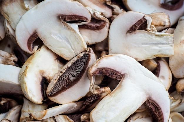 Arrière-plan de champignons et champignons hachés non frais. les produits en magasin de légumes ne sont pas le premier plan de fraîcheur. soyez prudent lorsque vous mangez des champignons.