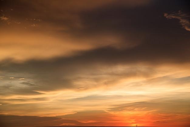 Arrière-plan de ciel orange et nuages avec lumière du coucher du soleil le soir à l'heure d'été avec un espace de copie vierge, montrant l'environnement, le concept climatique.