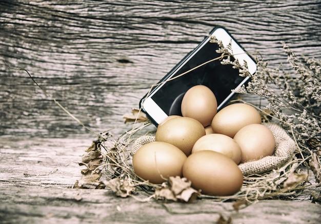 L'arrière-plan de conception d'art abstrait d'oeufs crus et de téléphone portable mis
