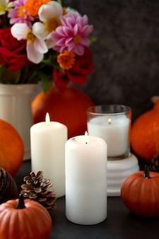 Arrière-plan créatif d'automne avec des bougies, des fleurs d'automne, des pommes de pin et des citrouilles. automne sombre et confortable