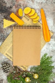 Arrière-plan de cuisine avec divers légumes et deux sortes de fromage sur un vieux journal sur fond de couleur mélangée