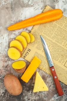 Arrière-plan de cuisson avec divers légumes et deux types de couteau à fromage sur un vieux journal