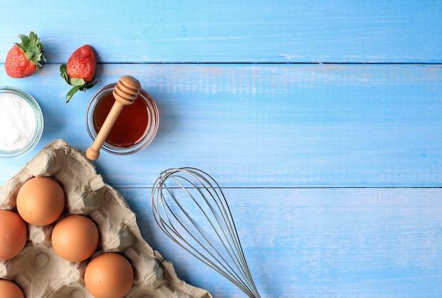 Arrière-plan de cuisson à mise au point sélective avec des ingrédients de cuisson tels que des œufs, des fraises, du citron, du sucre et du miel. convient pour le fond ou le papier peint sur fond bleu en bois
