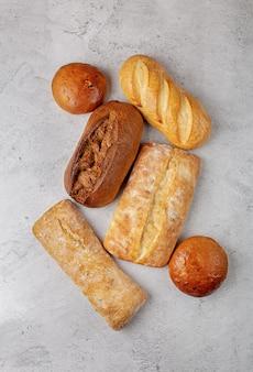 Arrière-plan de cuisson avec plusieurs miches de pain entières cuites au four vue de dessus sur la surface grise au centre