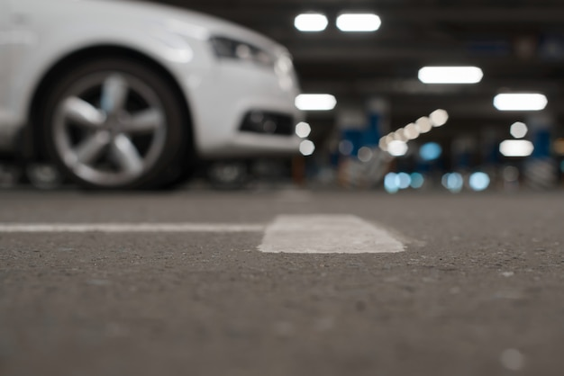 Arrière-plan défocalisé du parking souterrain, low angle view. les voitures garées et les lumières sont floues, mise au point sélective sur le sol.