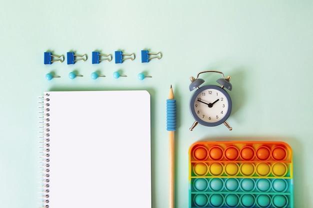Arrière-plan avec différentes fournitures scolaires sur fond bleu. concept de retour à l'école, vue de dessus.