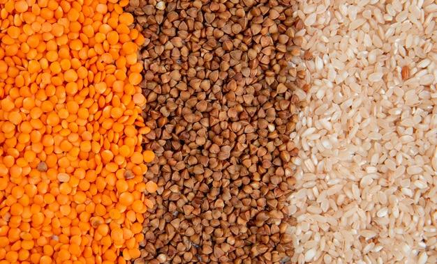 Arrière-plan de différents types de gruau lentilles rouges sarrasin et riz vue de dessus