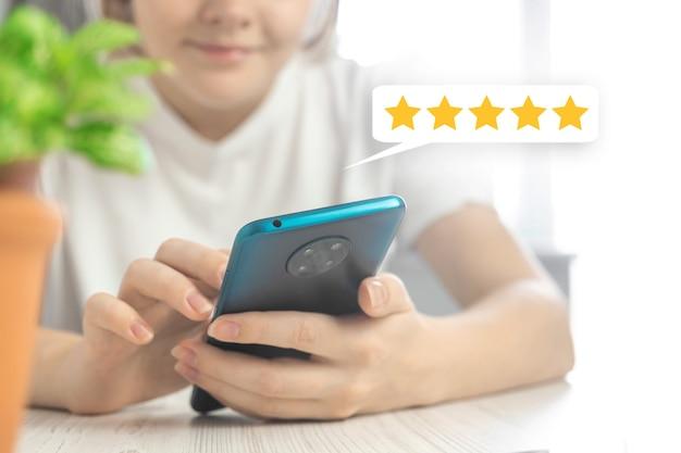 Arrière-plan du concept d'évaluation du service client, main de femme avec téléphone portable et icône de commentaires, examinez la photo du service