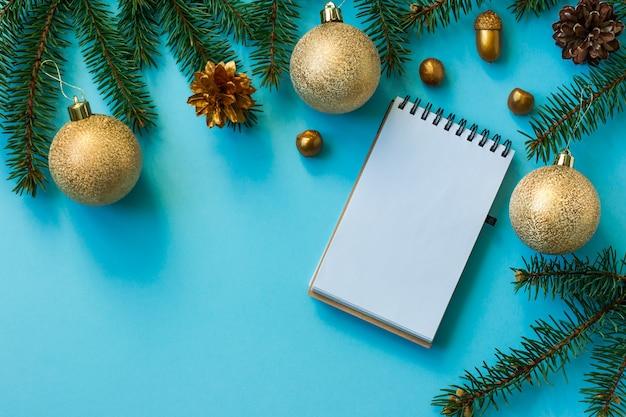 Arrière-plan du nouvel an avec des branches d'épinette, des boules dorées, des noix, des cônes, une mise en page de cahier. vue de dessus.