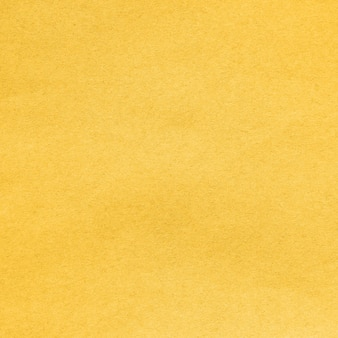 Arrière-plan de la feuille de carton recyclé à colorier dans la couleur tendance fortuna gold de l'année 2021. vue détaillée en gros plan texture abstraite recyclé modèle de matériau en carton écologique, toile de fond pour la conception