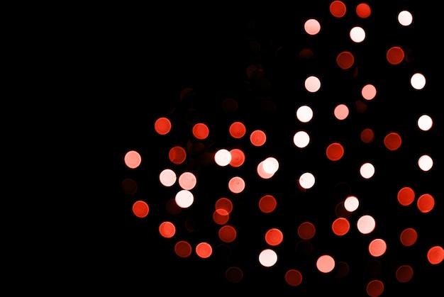 Arrière-plan flou abstrait lumières scintillantes avec forme de coeur sur fond noir.