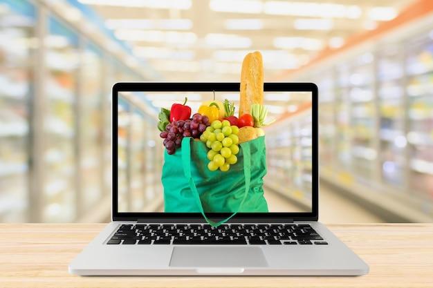 Arrière-plan flou allée de supermarché avec ordinateur portable et sac à provisions vert sur table en bois épicerie en ligne concept