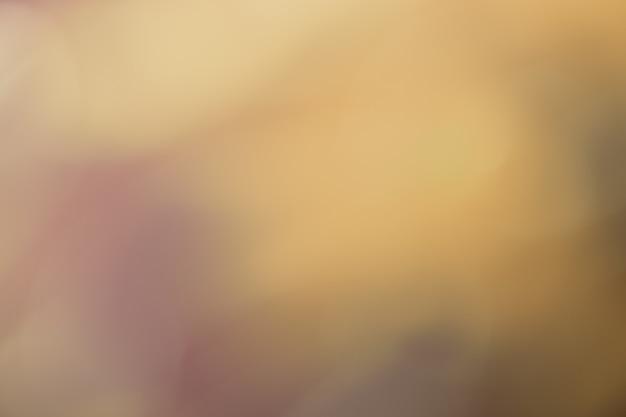 Arrière-plan flou beige foncé et doré. art défocalisé abstrait dégradé marron clair avec flou et bokeh. fond d'écran flou.