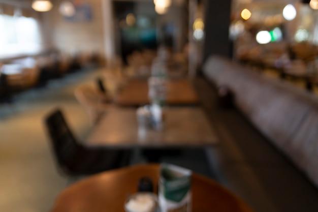 Arrière-plan flou d'un café abstrait avec des tables en bois et des lumières dorées en arrière-plan