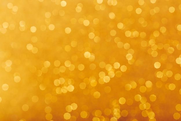 Arrière-plan flou d'étincelles brillantes dorées