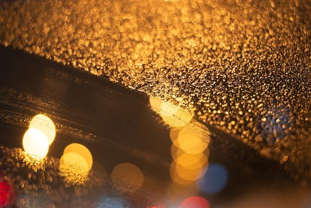 Arrière-plan flou avec des gouttes de pluie et des lumières.