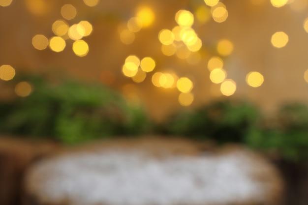 Arrière-plan flou de noël avec des lumières floues lumineuses et une surface en bois avec de la neige