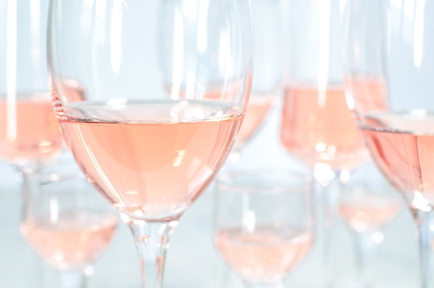 Arrière-plan flou de nombreux verres différents avec du vin rose.