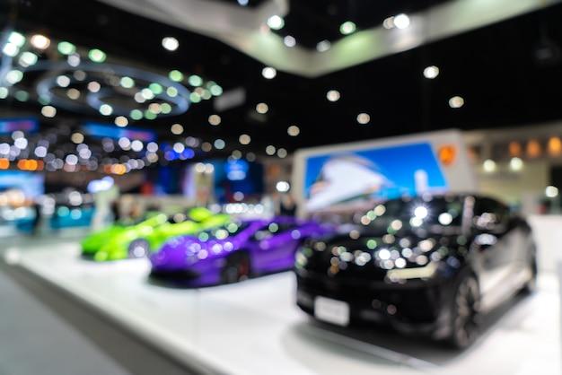 Arrière-plan flou de nouvelles voitures affichées dans la salle d'exposition de luxe avec bokeh léger