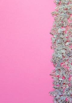 L'arrière-plan flou rose avec des paillettes argentées crée un cadre latéral. place pour votre conception. notion festive.
