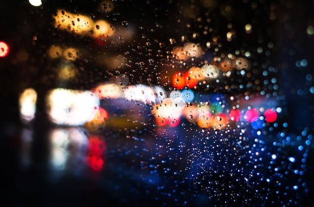 Arrière-plan flou de la rue de la ville de new york avec des gouttes d'eau et des néons à l'heure de la pluie le soir