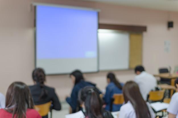 Arrière-plan flou de salle de classe éducative avec les étudiants et l'écran de projection