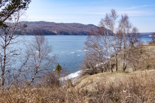 Arrière-plan flou vue paysage du lac baïkal avec arbres et montagnes en avril à kamen cherskogo, oblast d'irkoutsk, russie