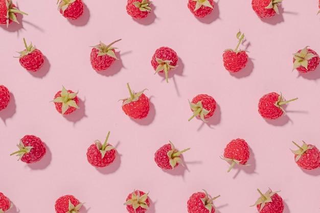 Arrière-plan de fruits frais avec des framboises rouges mûres disposées de manière aléatoire sur du papier rose dans une nature morte à plat