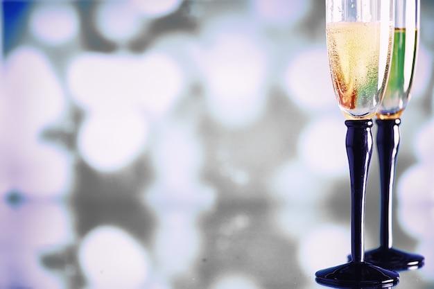 Arrière-plan avec de grands verres pour les vins mousseux. champagne et spray dans des verres en verre. boisson festive avec réflexion.