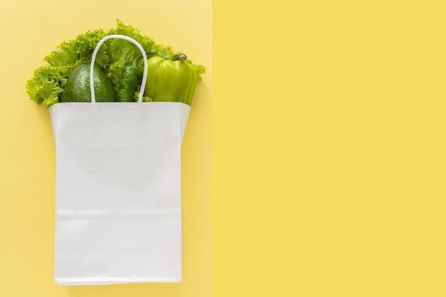 Arrière-plan de livraison d'aliments sains. nourriture végétarienne végétalienne dans des légumes en sac de papier blanc sur fond jaune. épicerie supermarché alimentaire et concept d'alimentation propre. vue de dessus. place pour le texte